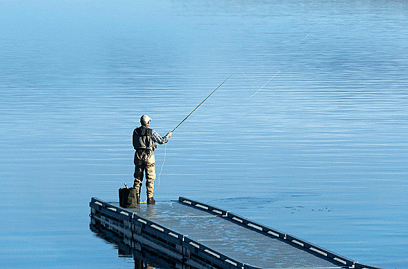 Man flyfishing from a floating dock