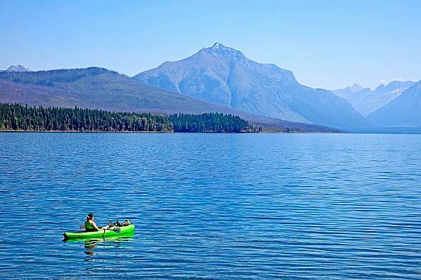 Kayaker floats alone in Lake McDonald in summer in Glacier National Park Montana