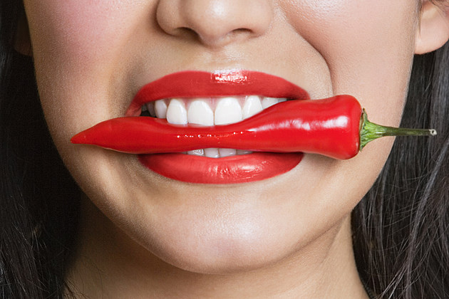 Close-up portrait of Hispanic woman biting red pepper